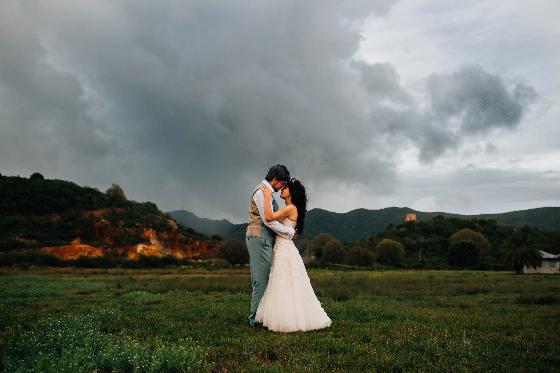 Antigua Destination Wedding Photography - Roxie & Mark - couple under moody sky and mountains