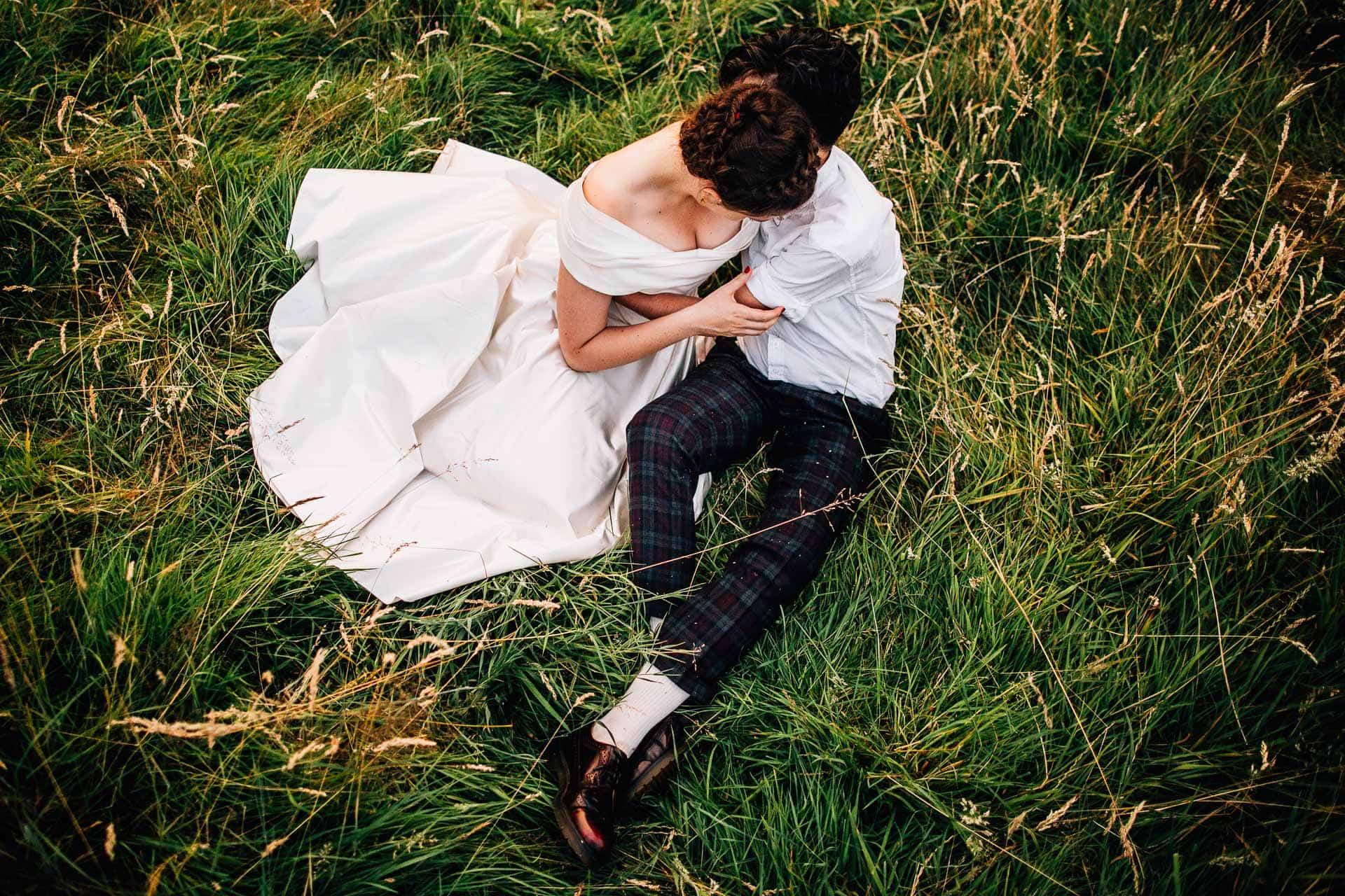 Blo Norton Hall Wedding Photography - K&L - katharine and lisa sat on the grass