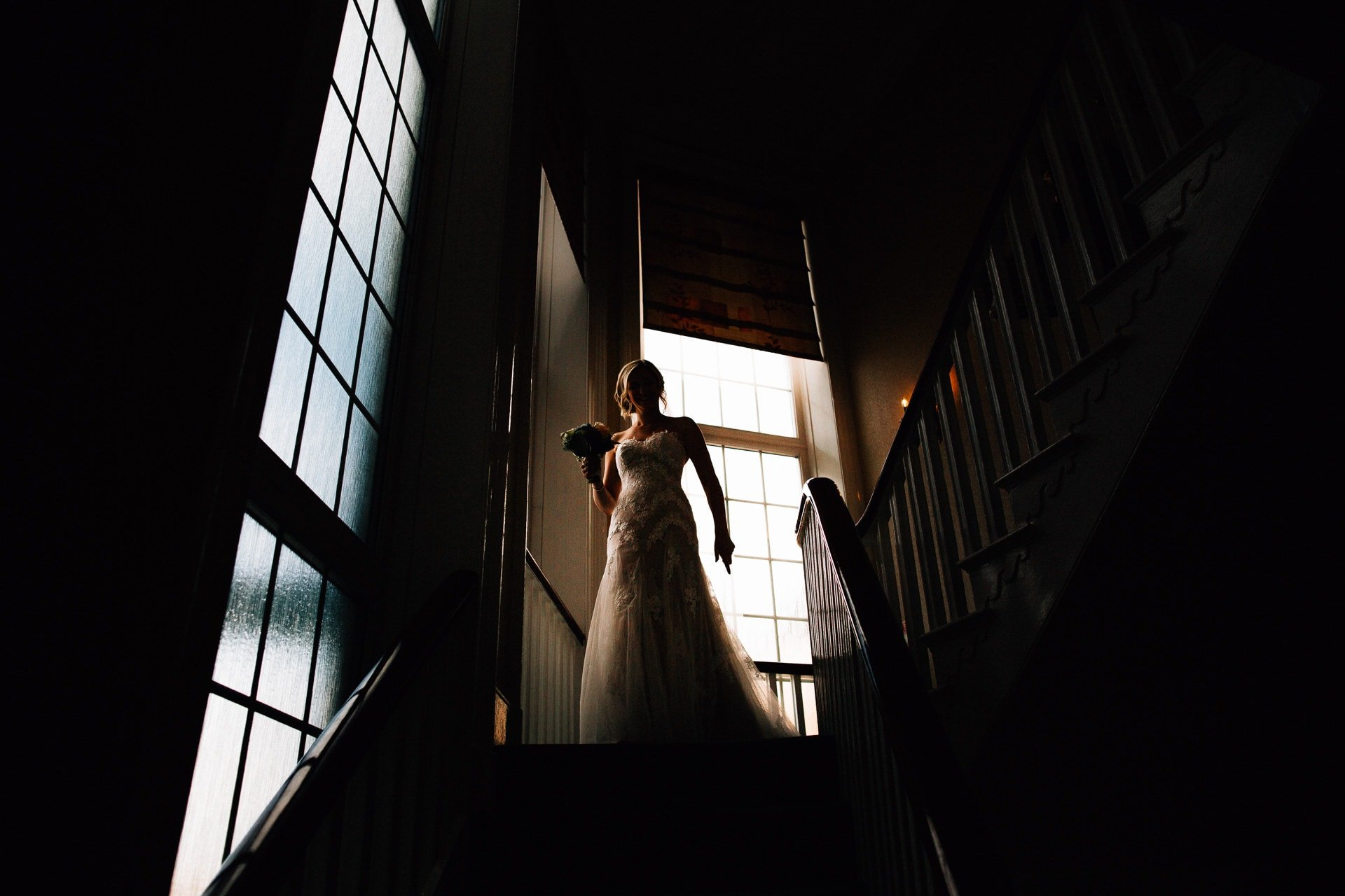 The Villa Wrea Green, Lancashire Wedding Photography - low key shot of bird e coming down the stairs