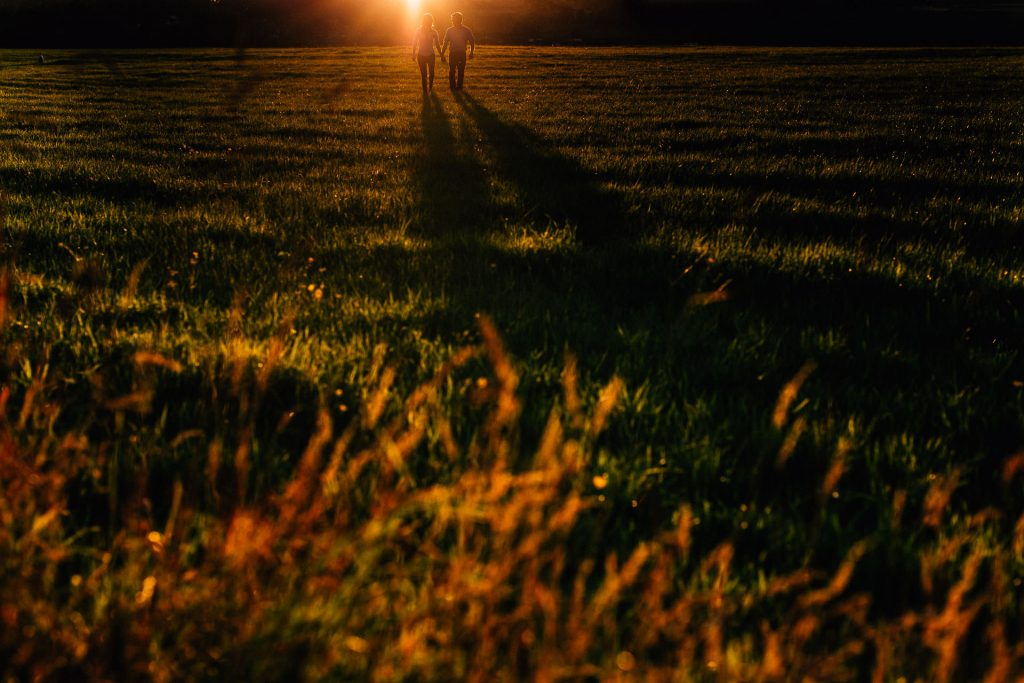 Lancashire Farm Pre Wedding Shoot - A&P - couple walking into a field at sunset