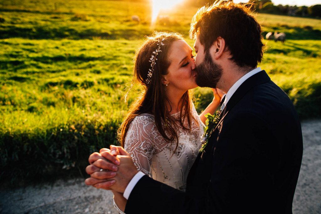 Lewes Castle Relaxed Farm Wedding Sussex - KB - bride and groom kissing at sunset