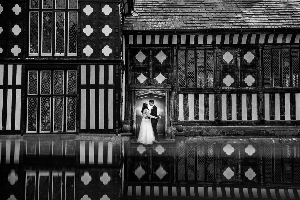 Rufford Old Hall Wedding Photography - L&C - portrait in front of the main doors to rufford old hall, black and white with reflection