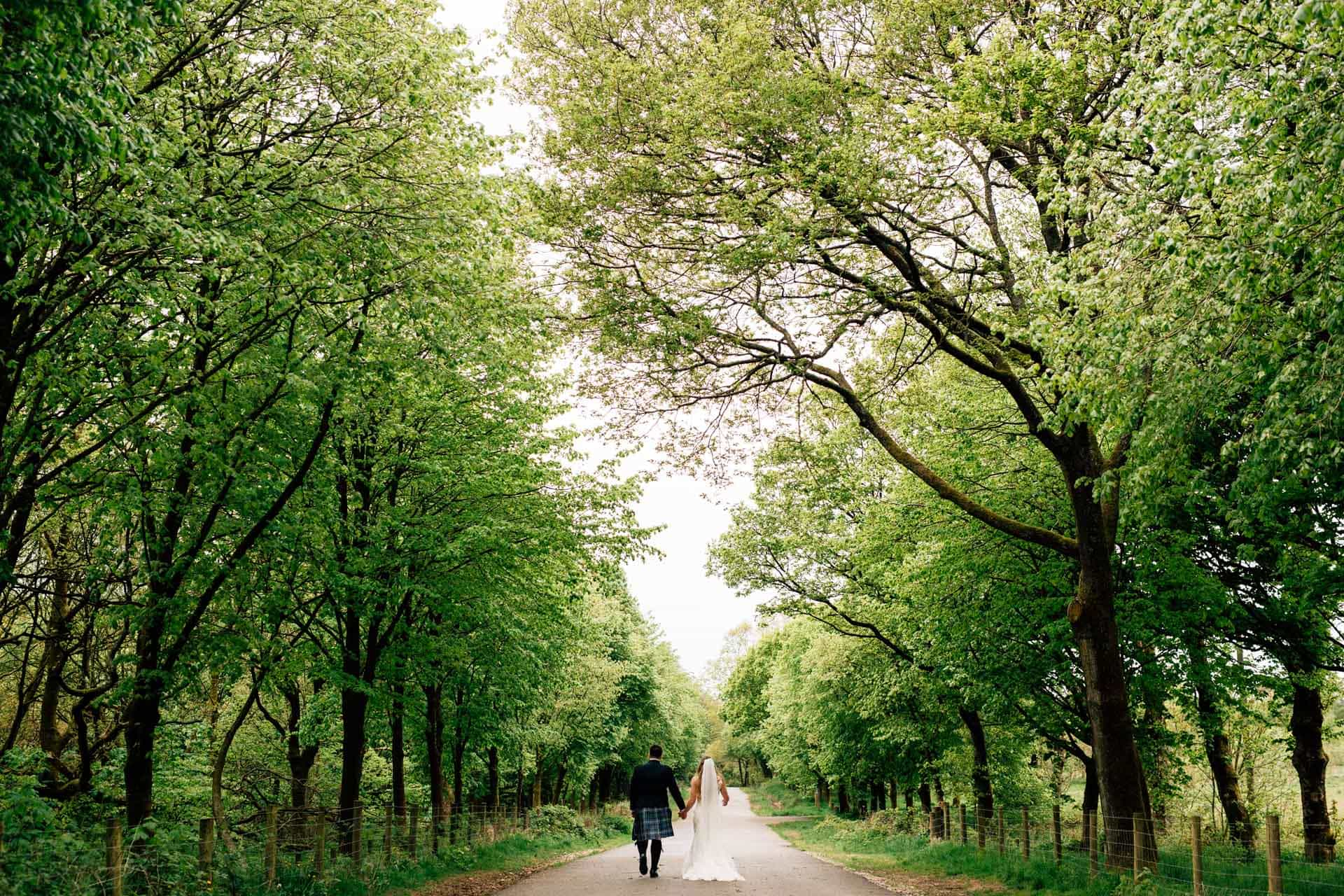Rivington Hall Barn Wedding Photography - AM - couple walking down woodland path